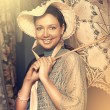 Woman in old hat with a lace umbrella — Stock Photo #18849233