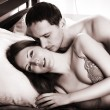Lovers couple kissing in bed - Stockfoto