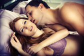 Lovers kissing in bed — Stock Photo