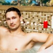Young man in romantic jacuzzi - Stockfoto