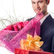 Man with flowers and gift — Stock Photo