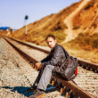 Young man with backpack on railroad — Stock Photo #19891295