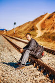 Young man with backpack on railroad — Stock Photo