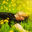 Man lying on grass at sunny day - Stock Photo