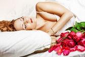 Slepping piękna kobieta z czerwonych róż — Zdjęcie stockowe