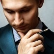 Businessman with pen thinking — Stock Photo