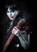 Dead female zombie with bloody axe — Stock Photo