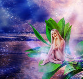 Beautiful sexy woman pixie on leaves — Stock Photo