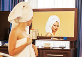 Woman with towel looking at the mirror — Stock Photo