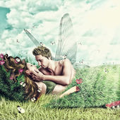 Loving fairy couple in a bed of grass — Stock Photo