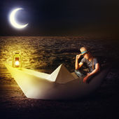 Man traveler sitting in fantasy paper boat — Stock Photo