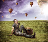Young man traveler and flying aerostats — Stock Photo