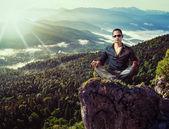 Junge mode-mann, sitzend auf berge-stein — Stockfoto