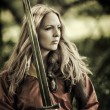 Sexy woman warrior with sword outdoor — Stock Photo #29436975