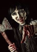 Female zombie with bloody axe — Stock Photo