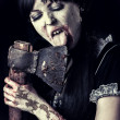 Female zombie licking bloody axe — Stock Photo #31764513
