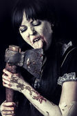 Female zombie licking bloody axe — Stock Photo