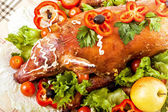 Christmas roast suckling pig on banquet table — Stock Photo