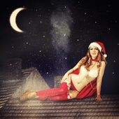 Christmas fairy woman in red dress and santa hat — Stock Photo