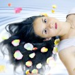 Nice girl in petals of roses on hair in spa — Stock Photo #3778666