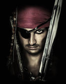 Handsome male pirate holding sword — Stock Photo