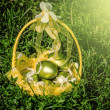 Basket of golden easter eggs on green grass — Stock Photo