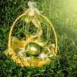 Basket of golden easter eggs on green grass — Stock Photo #41487371