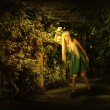 Постер, плакат: Young blond woman walking into enchanted forest