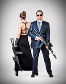Fashionable couple with automatics — Stock Photo