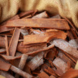 Big bag with cinnamon sticks in indian market — Photo