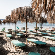 Loungers under palm tree leaves umbrellas on the beach — Stock Photo