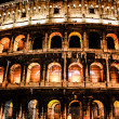 The Colosseum under the glow of lights at night, Rome - Stock Photo