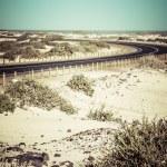 Winding desert road across the dunes of Corralejo, Fuerteventura, in the Canary Islands, Spain. — Stock Photo #27816673