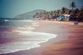 Exiting Anjuna beach panorama on low tide with white wet sand and green coconut palms, Goa, India — Stock Photo