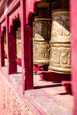 Buddhist prayer wheels in Tibetan monastery with written mantra. India, Himalaya, Ladakh — Stock Photo