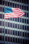 US american symbol flag over blue modern city buildings  — Stock Photo