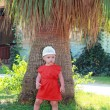 Beautiful baby girl standing near huge palm tree on summer natur — Stock Photo #13254042