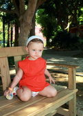 Thinking baby girl sitting on bench in red dress outdoor in park — Stock Photo