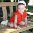 Fun baby girl in hat sitting on bench and looking with interest — Stock Photo #13279160