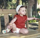 Tänkande flicka i klänning sitter på bänken och ser allvarlig — Stockfoto