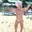 Fun baby joy on sand beach near the sea and holding hands up — Stock Photo #13338468