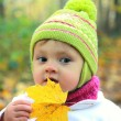 Fun baby in hat with maple leaf on autumn yellow background outd — Stock Photo #13428879