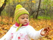 Baby girl in autumn yellow forest holding leaf and looking in ha — Stock Photo