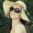 Royalty-Free Stock Photo: Smiling woman in hat and sun glasses looking happy on green back