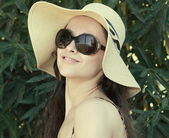 Smiling woman in hat and sun glasses looking happy on green back — Stock Photo