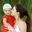 Beautiful mother kissing fun baby girl in hat outdoors green tre — Stock Photo #13648862