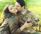 Happy couple drinking red wine outdoor. Man kissing laughing you — Stock Photo