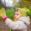 Smiling baby holding hand leaf on yellow autumn background - Stock Photo