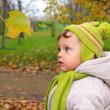 Fun baby looking on yellow leaf on autumn bright nature backgrou — Stock Photo #13785137