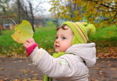 Smiling baby holding hand leaf on yellow autumn background — Stock Photo